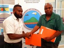 Director of Climate Change Mike Waiwai shaking hands with Director of Forestry Rexon Viranamanga during the MOU signing.